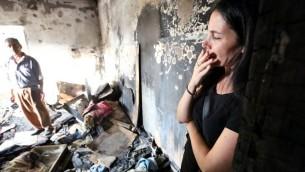 Une femme israélienne dans la maison brûlée de la famille Dawabsha à Duma à la suite de l'attaque terroriste de la semaine dernière, le 2 août 2015 (Crédit : Yossi Zamir / Flash90)