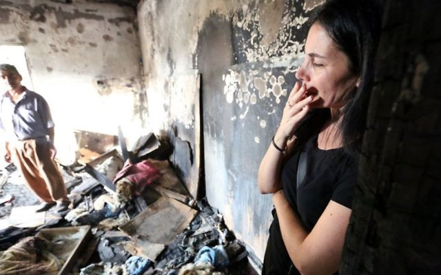 Une Israélienne dans la maison brûlée de la famille Dawabsha après l'attaque terroriste du 31 juillet 2015, à Duma, en Cisjordanie, le 2 août 2015. (Crédit : Yossi Zamir/Flash90)