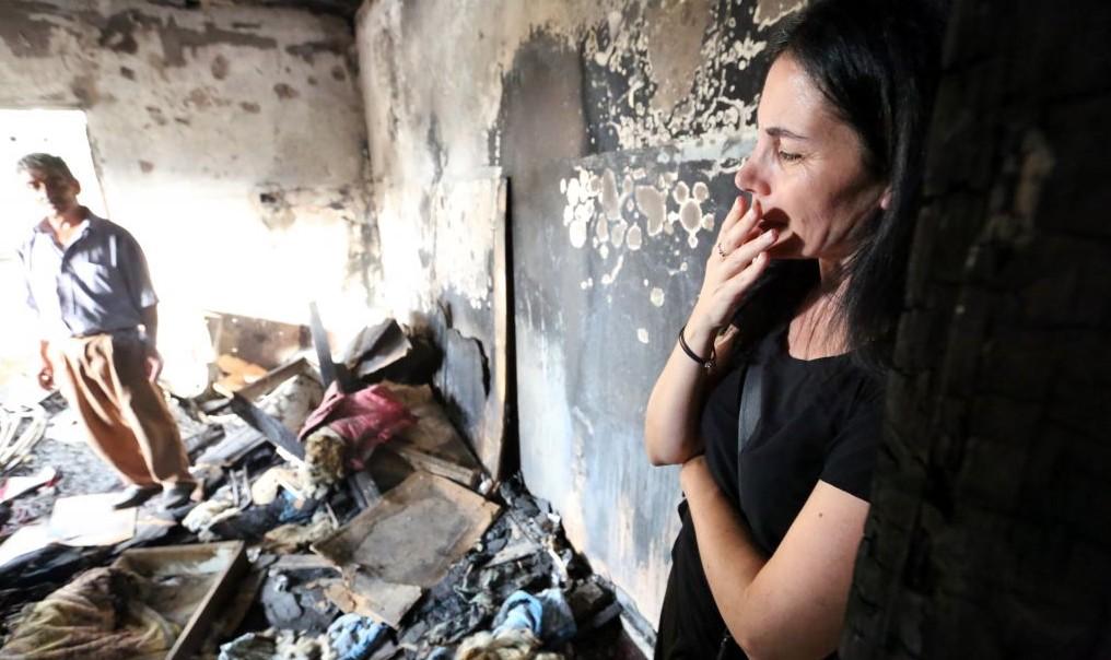 Une femme israélienne dans la maison brûlée de la famille Dawabsha à Douma à la suite de l'attaque terroriste de la semaine dernière, le 2 août 2015 (Crédit : Yossi Zamir / Flash90)
