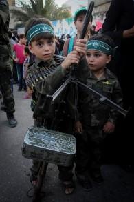 Un garçon palestinien porte l'arme de son père lors d'une cérémonie de remise des diplômes dans le cadre d'un camp d'été de style militaire organisée par le Hamas, le 5 août 2015 à Khan Yunis, dans le sud de la bande de Gaza. (Crédit : Abed Rahim Khatib / Flash90)