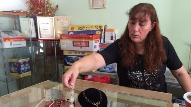 Vered Tartiks montre quelques-uns des bijoux qu'elle a fabriqué (Crédit : Luc Tress / Times of Israël)