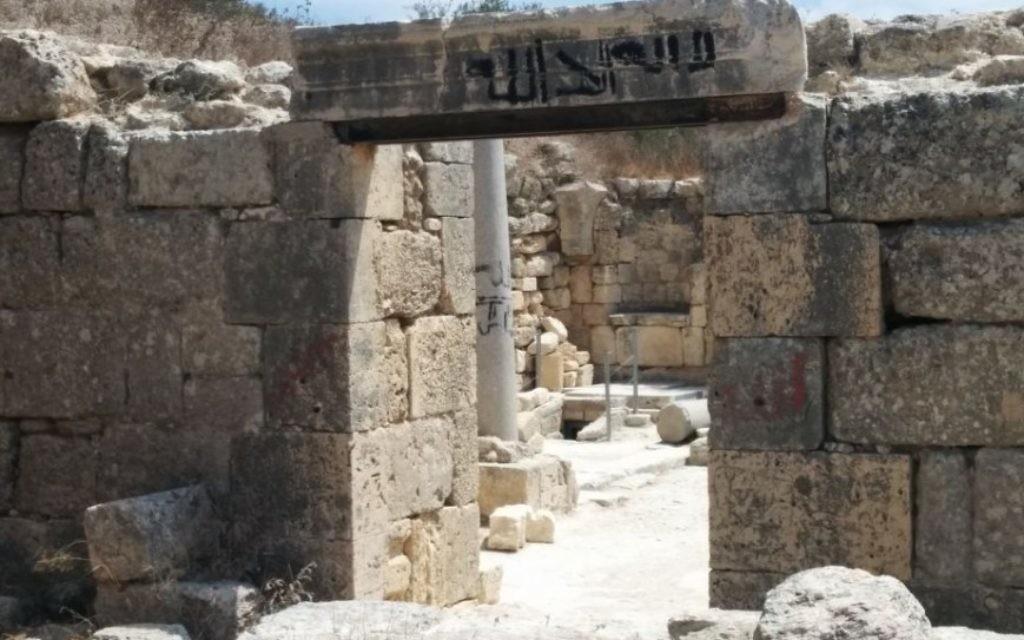 L'église saint Jean-Baptiste à Sebastia, en Cisjordanie,  barbouillée d'un grafitti en arabe (Crédit : Ilan Ben Zion/Times of Israel staff)