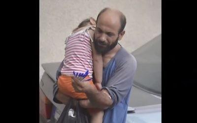 Le réfugié syrien-palestinien Adul Attar portant sa fille dans les rues de Beyrouth tout en vendant des stylos (Capture écran : YouTube)