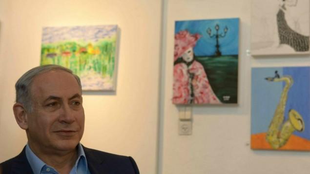 Le Premier ministre Benjamin Netanyahu visite une exposition de peintures d'Hadar Goldin, tombé dans une bataille à Gaza et dont le corps n'a pas été récupéré, au village d'artistes d'Ein Hod dans le nord d'Israël, le 10 août 2015. (Crédit : Amos Ben Gershom/GPO)