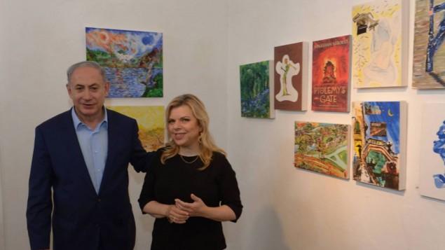 Le Premier ministre Benjamin Netanyahu et son épouse Sara visitent une exposition de peintures du lieutenant Hadar Goldin, disparu pendant l'opération Bordure protectrice à Gaza en août 2014, dans le village d'artistes d'Ein Hod dans le nord d'Israël, le 10 août 2015. (Crédit : Amos Ben Gershom / GPO)