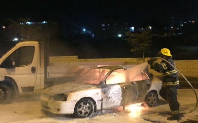 Les pompiers éteignent une voiture qui a pris feu après avoir été touchée par un cocktail Molotov à proximité du quartier arabe de Beit Hanina à Jérusalem-Est, blessant trois personnes, lundi soir, le 3 août 2015 (Sliman Khader / FLASH90)