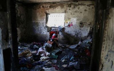 L'intérieur d'une chambre de la maison de la famille Dawabsha à Duma. Une poupée enveloppée dans un drapeau palestinien repose dans une poussette en l'honneur d'Ali (Crédit : Eric Cortellessa / Times of Israel)