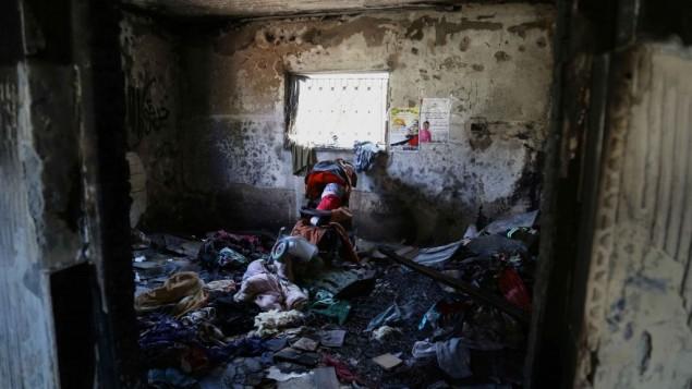 L'intérieur la chambre attaquée de la maison Dawabsha à Duma. Une poupée enveloppée dans un drapeau palestinien repose dans une poussette pour honorer Ali (Crédit : Eric Cortellessa / Times of Israel)
