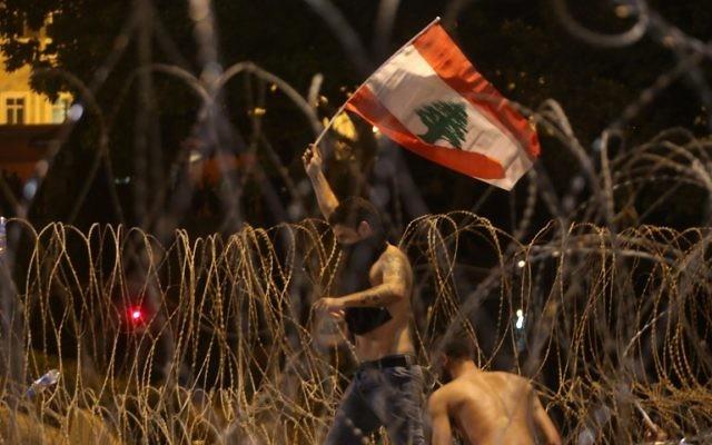 Un Libanais agite un drapeau national alors qu'il tente de franchir les barbelés séparant les manifestants du palais gouvernemental lors d'un rassemblement de masse contre une classe politique considérée comme corrompue et incapable de fournir les services de base le 29 août 2015 sur la place des Martyrs de Beyrouth. (AFP PHOTO / STR)