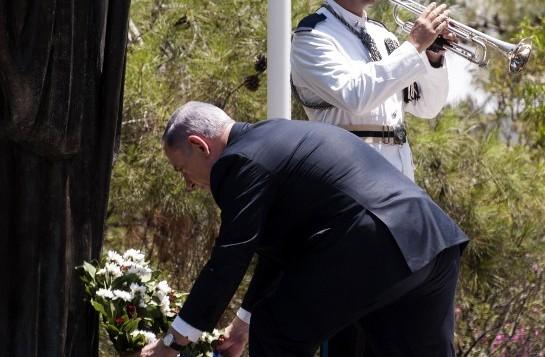 Le Premier ministre israélien Benjamin Netanyahu (au centre) dépose une couronne devant la statue de l'ancien président de la République de Chypre l'archevêque Makarios III à son arrivée le 28 juillet 2015 (Crédit : AFP PHOTO / IAKOVOS HATZISTAVROU)