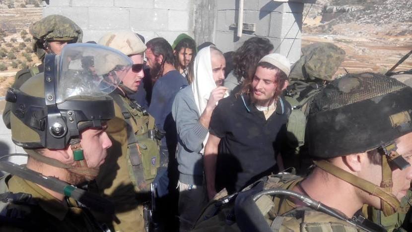 Meir Ettinger, en kippa blanche, escorté par des soldats de Tsahal dans le village cisjordanien de Qusra, le 7 janvier 2014 (Crédit : Zacharie, Rabbins pour les Droits de l'Homme)