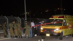 Les forces de sécurité israéliennes autour du corps d'un Palestinien qui a été abattu après avoir poignardé un Israélien le dimanche soir, 9 août 2015 à une station d'essence sur la route 443 qui mène à Jérusalem (Credit photo: Yonatan Sindel / Flash90)