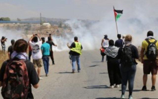 Des manifestants dans le village de Nabi Saleh en Cisjordanie face à des tirs de gaz lacrymogène après avoir jeté des pierres sur les soldats de Tsahal (Photo: Eric Cortellessa / Times of Israel)