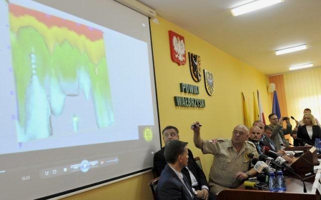 Krzysztof Szpakowski (3ème à gauche) présente l'image au géoradar d'un tunnel lors d'une conférence de presse concernant la découverte d'un nouveau tunnel, qui fait partie d'une des structures souterraines dont le but est inconnu pendant la Seconde Guerre mondiale par l'Allemagne nazie, le 11 septembre 2015 à Walbrzych (Crédit : AFP PHOTO / Piotr Hawalej)