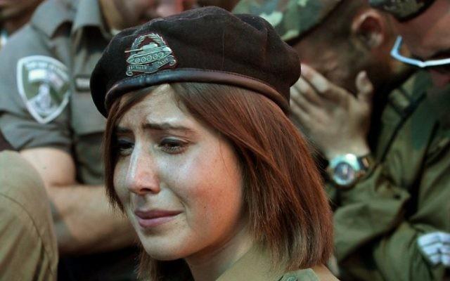Des soldats et des amis israéliens pleurent lors des funérailles du caporal de soldat israélien Meidan Maymon Biton, 20 ans, au cimetière de la ville de Netivot le 29 juillet 2014. Meidan a été tué la veille quand un obus de mortier a été tiré à partir de la bande de Gaza et qui a frappé le conseil régional d'Eshkol (Crédit : Gil Cohen-Magen / AFP)