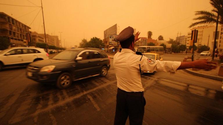 Un policier irakien régule la circulation dans une rue de la capitale Bagdad pendant une tempête de sable le 1er Septembre 2015 (Crédit : AFP Photo / Haidar Mohammed Ali)