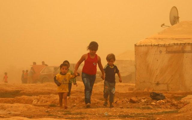 Les enfants syriens à pied au milieu de la poussière pendant une tempête de sable le 7 septembre 2015 au camp de réfugiés en périphérie de la ville libanaise  de Baalbek. (Crédit : AFP PHOTO / STR)