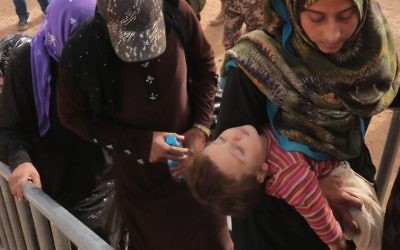 Des réfugiés syriens attendent au camp de fortune d'al-Roqban, sur la frontière avec la Syrie, avant d'être chassés par l'armée jordanienne de la ville orientale de Ruwaished où ils seront accueillis et contrôlés par les autorités jordaniennes le 10 septembre, 2015. Le dernier lot de réfugiés de la Syrie voisine sera envoyé à Ruwaished, à environ 380 km de la capitale Amman, à divers camps de réfugiés et des campements temporaires à travers le pays. (Crédit : AFP PHOTO / KHALIL MAZRAAWI)