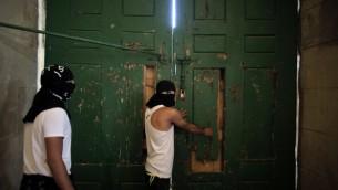 Les Palestiniens masqués sécurisant la porte de la mosquée al-Aqsa le 27 septembre 2015 (Crédit : AFP PHOTO / AHMAD GHARABLI)