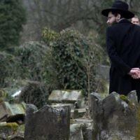 Un membre de la communauté juive devant les pierres tombales brisées après la profanation de quelque 250 tombes, suite à  une cérémonie au cimetière juif de Sarre-Union, à l'est de la France, le 17 février 2015. (Crédit : Patrick Hertzog/AFP)