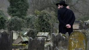 Un membre de la communauté juive se penche sur les pierres tombales brisées suite à  une cérémonie au cimetière juif de Sarre-Union, à l'est de la France, le 17 Février 2015, après la profanation de quelque 300 tombes. (AFP / PATRICK HERTZOG)
