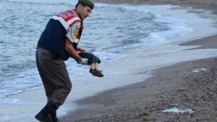 Un officier de police turc porte le cadavre d'un enfant migrant au large des côtes à Bodrum, au sud de la Turquie, le 2 septembre 2015 (Crédit : AFP / DOGAN AGENCE DE NOUVELLES)