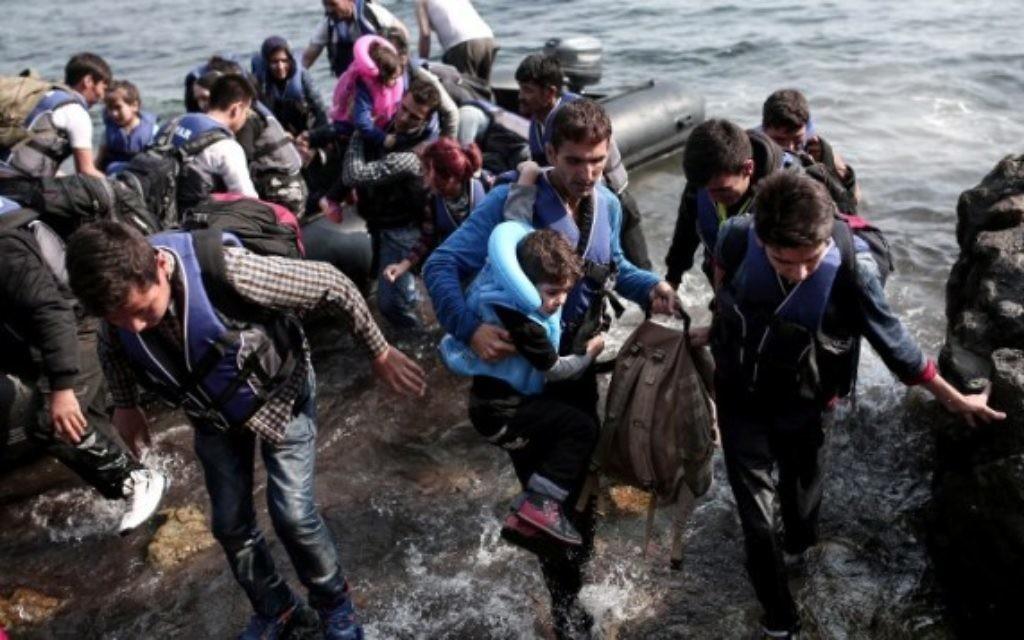 Des réfugiés syriens accostent sur l'île de Lesbos, après avoir traversé la mer Egée, le 3 septembre 2015 (Crédit : ANGELOS TZORTZINIS/ AFP)