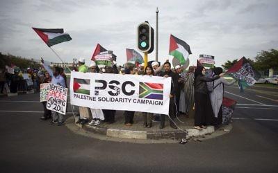 Des personnes brandissant des drapeaux palestiniens et une banderole « Palestine Solidarity Campaign » lors d'une manifestation contre le chanteur américain Pharrell Williams, près du Grand Casino où il tenait un concert au Cap, le 21 septembre 2015 (Crédit : AFP PHOTO / RODGER BOSCH)