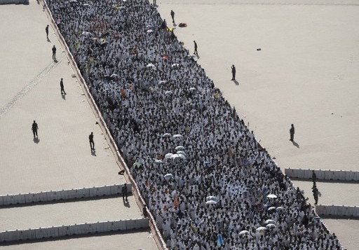"""Pèlerins musulmans jetant des cailloux pendant le rituel du """"Djamarat"""", la lapidation de Satan, à Mina, près de la ville sainte de La Mecque, le 4 octobre 2014. (Crédit : Mohammed al-Shaikh/AFP)"""