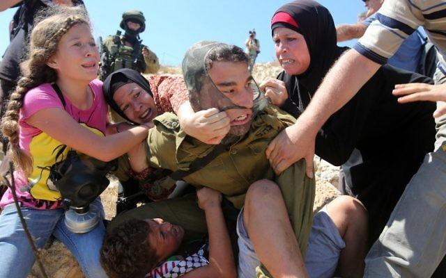 Des Palestiniens combattant un soldat israélien qui a tenté d'arrêter un garçon lors d'une manifestation près du village cisjordanien de Nabi Saleh, près de Ramallah, le 28 août 2015 (Crédit : AFP Photo / Abbas Momani)