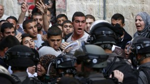 Des Palestiniens crient en face de forces de sécurité israéliennes qui bloquent une route menant à l'enceinte de la mosquée Al-Aqsa dans la Vieille Ville de Jérusalem, le 13 septembre 2015 (Crédit Photo : Ahmad Gharabli / AFP)