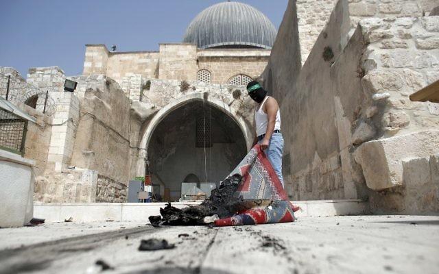 Un Palestinien masqué portant un bandeau du Hamas sort un tapis brûlé de la mosquée Al-Aqsa dans la Vieille Ville de Jérusalem lors des affrontements dans l'enceinte le 13 septembre 2015, quelques heures avant le début de la nouvelle année juive (Crédit : AFP PHOTO / AHMAD GHARABLI)