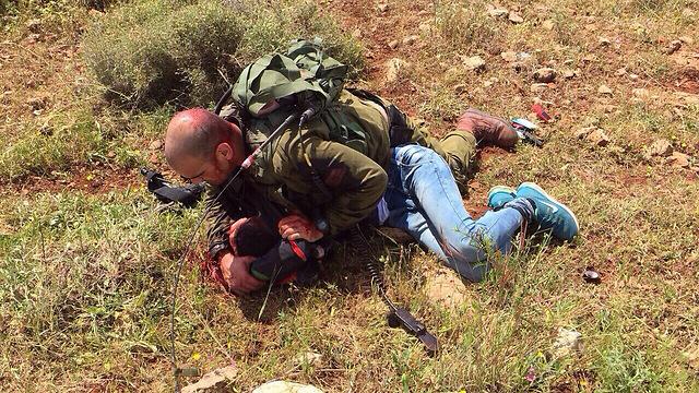 Un soldat israélien neutralise un Palestinien qui a poignardé un autre soldat près de la barrière de sécurité en Cisjordanie le 2 avril 2015 (Crédit : Porte-parole de Tsahal)