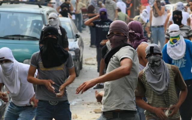 Des jeunes arabes jetant des pierres sur des forces de sécurité israéliennes lors d'affrontements à Jérusalem-Est  (Crédit photo: Kobi Gideon / Flash90)