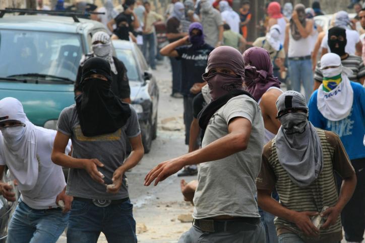 Des jeunes arabes jetant des pierres sur des forces de sécurité israéliennes lors d'affrontements à Jérusalem-Est. (Crédit : Kobi Gideon / Flash90)