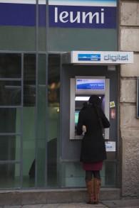 Une femme se tient devant un guichet automatique à Jérusalem (Crédit: Yonatan Sindel / Flash90)