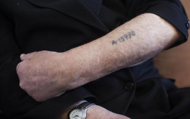 Un survivant de l'Holocauste montre son numéro de prisonnier tatoué sur son bras. (Crédit : Yonatan Sindel / Flash90)