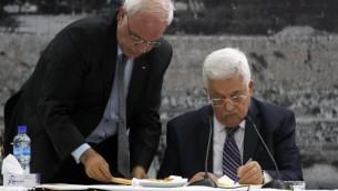 Le président de l'Autorité Mahmoud Abbas, à droite, signe une demande d'adhésion à 15 instances onusiennes et d'autres traités internationaux dans son quartier général dans la ville de Ramallah en Cisjordanie, le mardi 1er avril 2014. avec à ses côtés Saeb Erekat (Crédit : Issam Rimawi / Flash90)