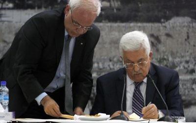 Le président de l'Autorité Mahmoud Abbas, à droite, signe une demande d'adhésion à 15 instances onusiennes et d'autres traités internationaux dans son quartier général dans la ville de Ramallah en Cisjordanie, le mardi 1er avril 2014. avec à ses côtés Saeb Erekat (Crédit : Issam Rimawi/Flash90)