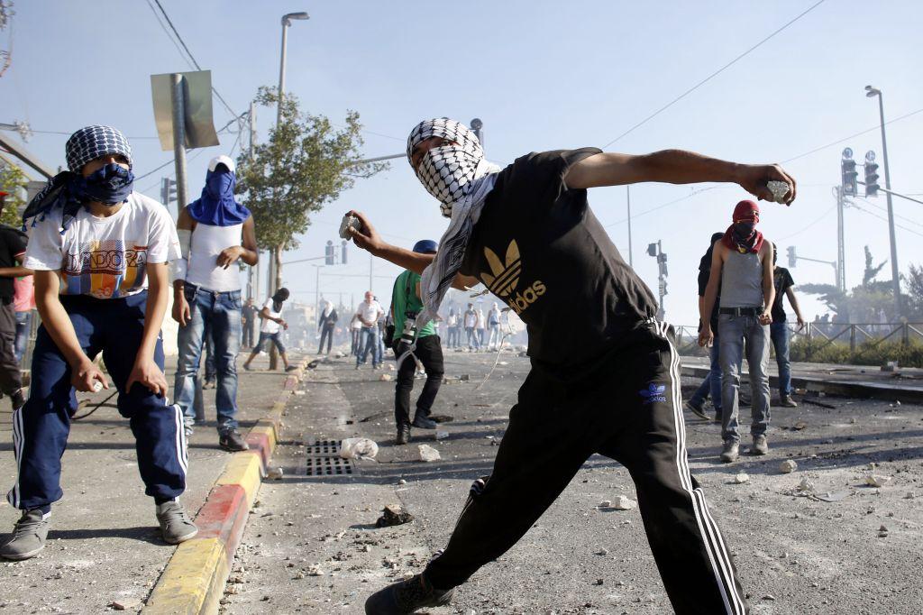 Des manifestants palestiniens masqués jetant des pierres sur la police israélienne lors d'affrontements dans le quartier de Shuafat à Jérusalem-Est, le 3 juillet 2014 (Crédit : Sliman Khader / Flash90)