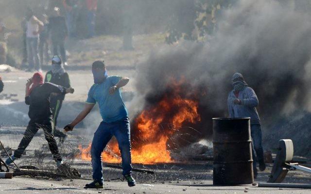 Les manifestants jetant des pierres sur les agents de la police des frontières israélienne à l'entrée de Kafr Kanna le 9 Novembre 2014 (Crédit: Flash90)
