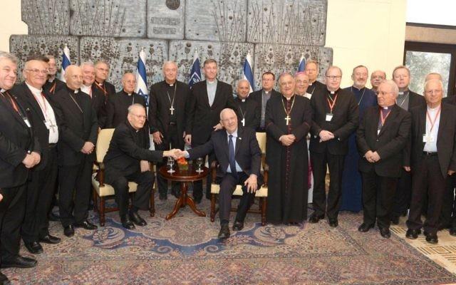 Le président Reuven Rivlin (assis, au centre à droite) à sa résidence avec les membres de la Commission épiscopale de la communauté européenne, serre la main du président de la commission, le Cardinal Péter Erdö, à Jérusalem, le 16 septembre 2015 (Crédit : Michael Nyman / GPO )
