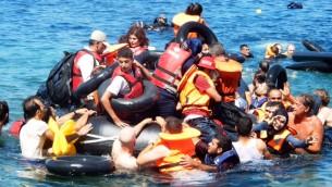 Le personnel d'IsraAID aidant les réfugiés à atteindre le rivage après que leur bateau se soit renversé au large de la côte grecque, le 13 septembre 2015 (Crédit : Autorisation  d'IsraAid)