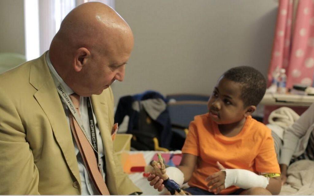 Dr L. Scott Levin pendant une visite post-opératoire avec  Zion Harvey, 8 ans, qui a subi une greffe de la main bilatérale en juillet 2015 au Centre hospitalier pour enfants de Philadelphie. (Crédit :  CHOP)