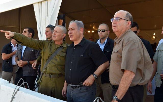 Le Premier ministre Benjamin Netanyahu (au centre) et le ministre de la Défense Moshe Yaalon (à droite), en visite le long d'une clôture prévue le long de la partie sud de la frontière entre Israël et la Jordanie, le 6 septembre 2015 (Crédit : Ariel Harmoni / Ministère de la Défense)