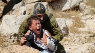 Un soldat de Tsahal tente d'arrêter un garçon de 12 ans, accusé d'avoir jeté des pierres, lors d'une manifestation dans le village de Nabi Saleh en Cisjordanie (Photo: Eric Cortellessa / Times of Israel)