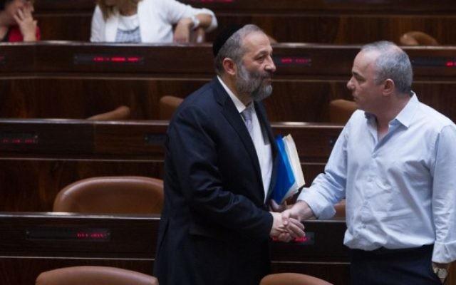 Le ministre de l'Economie Aryeh Deri parle avec le ministre de l'Energie Youval Steinitz lors d'une session plénière à la Knesset le 17 juin 2015. (Miriam Alster/ FLASH90)