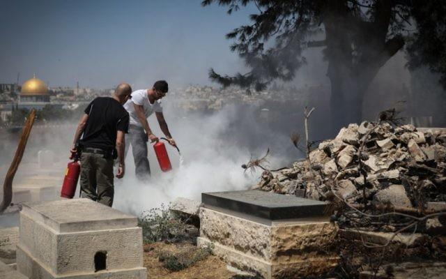 Les forces de sécurité tentent d'éteindre un incendie qui a éclaté dans le cimetière juif du Mont des Oliviers, où plusieurs pierres tombales auraient été profanées et mises à feu pendant la nuit, le 2 septembre 2015 [Hadas Parush / Flash90]