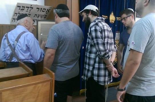 Pessah Steiner, 92 ans, le gabbaï de la synagogue, montre un peu l'histoire des lieux aux volontaires qui ont nettoyé le bâtiment. (Crédit: Autorisation Eli Naiditch)