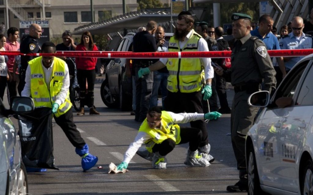Des secouristes israéliens là où un Palestinien a poignardé un soldat israélien à plusieurs reprises dans une attaque terroriste, à la gare HaHagana de Tel-Aviv, le 10 novembre 2014. (Crédit : Amir Levy/Flash90)